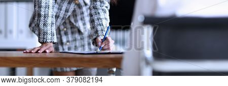 Slender Woman Stands In Office And Signs Document. Employee Training, Continuing Education. Professi