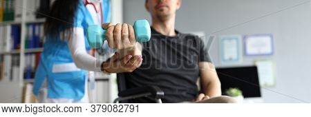 Man On Wheelchair Holds Dumbbell In His Hands. Doctor And Young Man In Wheelchair. Treatment And Res