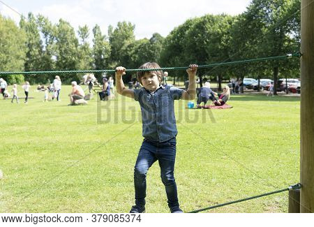Active Kid Holding Robe In Playground, Child Enjoying Activity In A Climbing Adventure Park On Summe