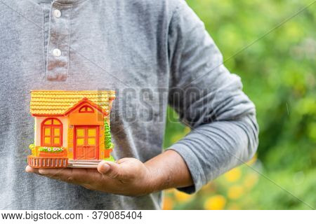 Hand Holding Piggy Bank (home Model) In Rainy Days On Green Nature Blur Background. Home Protect And