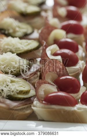 Canapes Prepared On A Platter, Garnished With Salami, Cucumber, Tomato, Pepper And Grated Cheese.