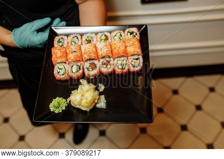 Hand Waiter Holding Set Delicious Fresh Sushi Slate Plate, Japanese Raw Fish In Traditional Restaura