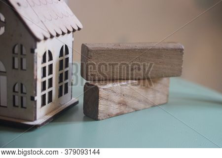 Miniature Wooden Toy House And Two Wooden Building Blocks. Real Estate Concept