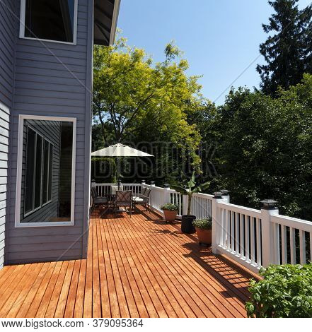 Outdoor Home Wooden Deck Patio During Lovely Summer Day With Seasonal Garden
