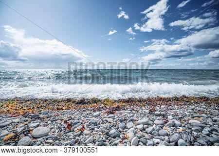 Nordic Beach With Pebbles And Seaweed With Waves Coming In On The Shore Under A Blue Sky