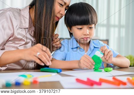 Asian Mother Work Home Together With Son. Mom And Kid Play Dough. Child Creating Plasticine Clay Mod