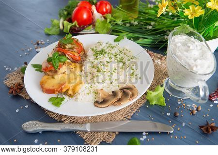 Fired Cordon Bleu Chicken Served With Rice And Parsley On Plate.