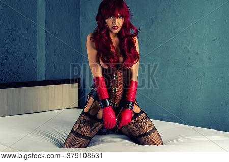 Redhead Slave Woman In A Red Wig, Corset And Leather Gloves Posing On A Bed. Legs Are Bound With Bon