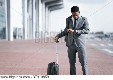 Concerned Black Businessman With Travel Suitcase Checking Time On Watch Waiting For Delayed Flight A