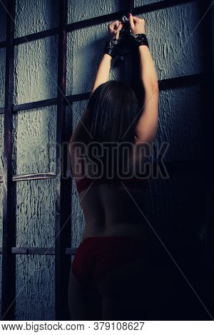 Bdsm Outfit For Adult Sex Games. A Young Woman Chained To The Bars With Handcuffs With Bondage Await