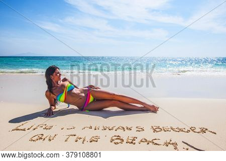 Woman in bikini lies on sea beach , Life is always better on the beach, conceptual handwriting on sand