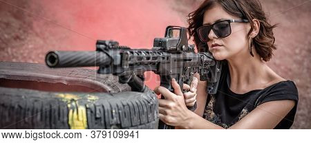 Attractive Woman Shooting With Rifle Machine Gun From Behind Barricade