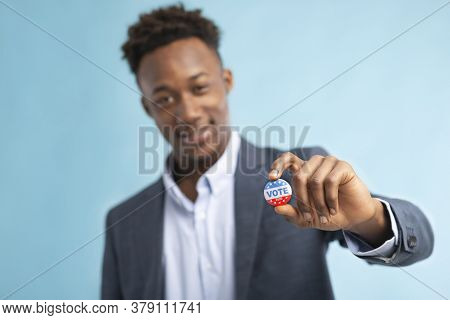 Us Presidential Election 2020 Vote. African American Man Showing Vote Pin, Blurred Background