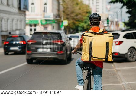 Urban Transport, Traffic And Deliveryman. Male Courier With Helmet And Big Yellow Backpack Ride On B