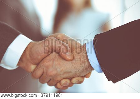 Business People Shaking Hands While Standing With Colleagues After Meeting Or Negotiation, Close-up.