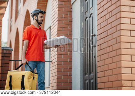 Courier Delivers Pizza To Front Door. Young Deliveryman With Safety Helmet Holding Large Yellow Bag