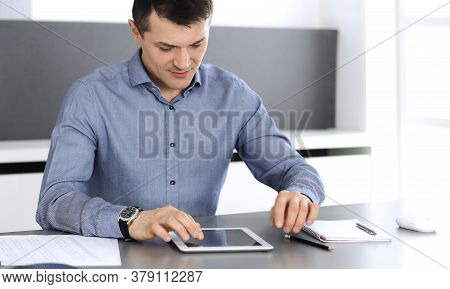 Businessman Working With Tablet Computer In Modern Office. Headshot Of Male Entrepreneur Or Company