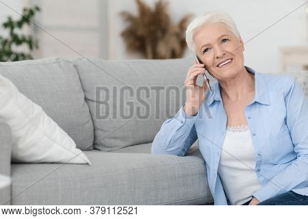 Concierge Services Concept. Smiling Senior Woman Talking On Cellphone With Personal Assistant Manage