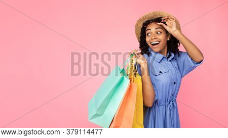 Excited African American Girl On Shopping Carrying Shopper Bags Looking Aside At Copyspace Posing In