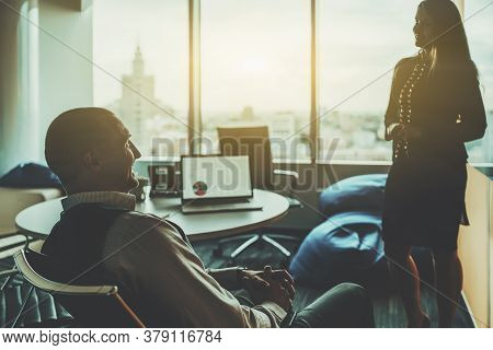 Silhouettes Of Two Businesspeople Having A Meeting In A Typical Boardroom On The High Floor Of A Con