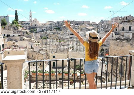 Happy Tourist Girl With Arms Raised Up Enjoys The Stunning View Of The Sassi Di Matera In Italy On A