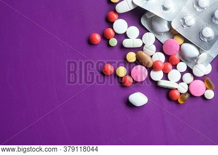 Close Up Of Colorful Pills Spilling On Purple Background