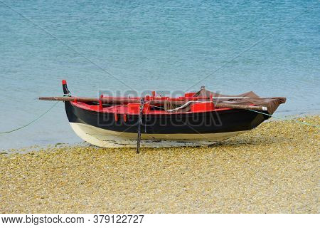 Black Wooden Fishing Boat Dries Up On The Seashore