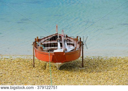 Red Wooden Fishing Boat Dries On The Seashore