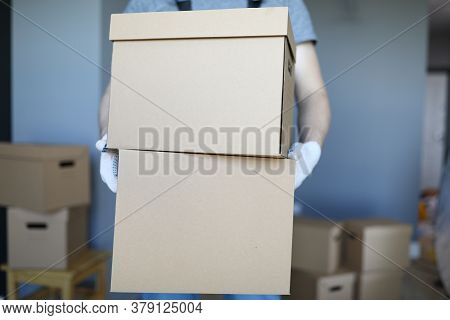 Close-up Of Male Carrying Cardboard Boxes In Gloves. Delivery Service. Unpacked Personal Things In C