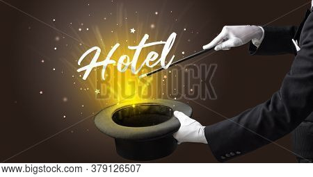 Magician is showing magic trick with Hotel inscription, traveling concept