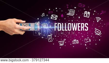 hand holding wireless peripheral with FOLLOWERS inscription, social media concept