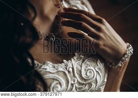 Portrait Of The Bride. The Young Bride Holds On To The Pendant Around Her Neck. The Brides Face Is H
