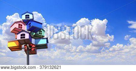 Horizontal banner with colorful nesting boxes on blue sky background. Many birdhouses of different colors and blue sky with clouds
