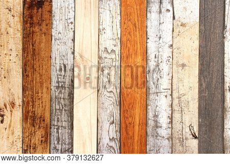 Texture of ancient wall with wooden planks of different color and cracked paint of white color