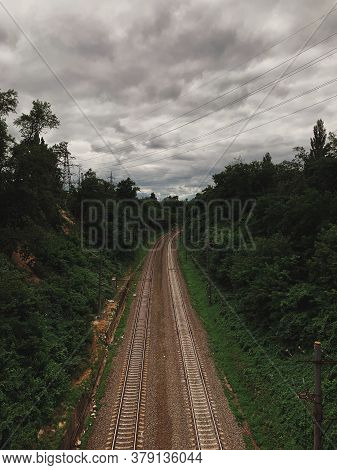 Railroad Tracks Recede To The Horizon, Dark Summer Sky Approaching