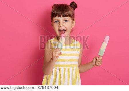 Little Girl Holding And Eating Two Ice Cream, Keeping Mouth Widely Opened And Biting Water Ice, Look