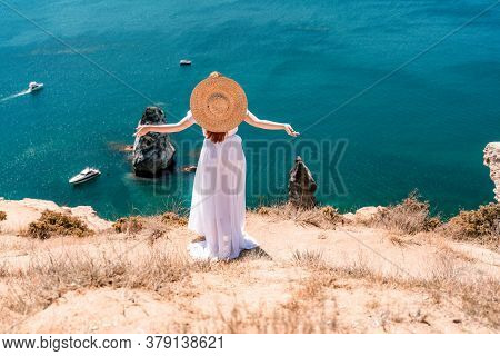 From Behind, A Woman Is Seen In A White Flying Dress Fluttering In The Wind. In A Straw Hat, Walking