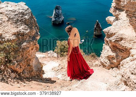 From Behind, A Woman Is Seen In A Red Flying Dress Fluttering In The Wind. In A Straw Hat, Walking D