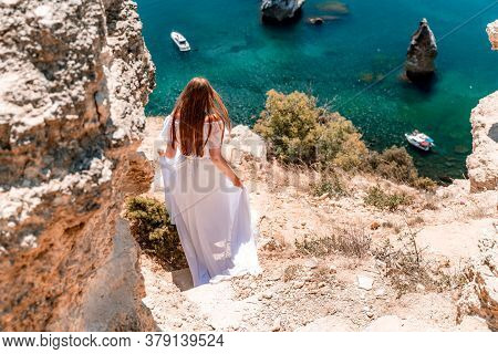 A Woman In A White Flying Dress Is Seen Behind, Fluttering In The Wind. Going Down The Stairs Agains