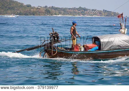 Phuket, Thailand, February 04, 2020: Thai Captain Drives A Traditional Wooden Boat