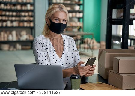 Female Business Owner Wearing Protective Face Mask Holding Mobile Phone And Looking At Camera While