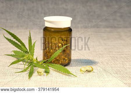 Green Leaves Of Medicinal Cannabis And Oil Extract In A Jar With Capsules