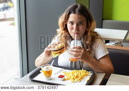 Junk Food Is Comfort Food. Asian Young Girl Eating Fast Food And Drinking Milkshake Indoors With Ple