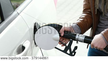Close view of women hand holding fuel nozzle and refueling the car. Petroleum business.