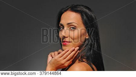 Smiled woman touching face while standing on black background. Side view.