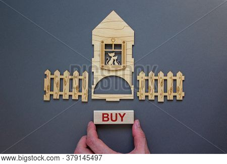 Model Of A Wooden House. Word 'buy' On Wooden Block. Male Hand, Wooden Fence. Copy Space. Business C