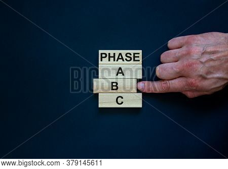 Wooden Blocks Form The Words 'phase, A, B, C' On Black Background. Male Hand. Beautiful Background.