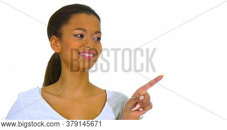 Mixed race woman showing with finger on empty space, on side.