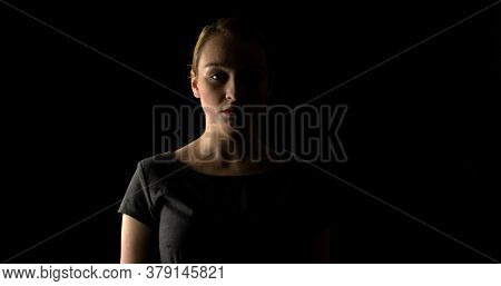 Expression of woman's face in dark shadow. Emotional problems.
