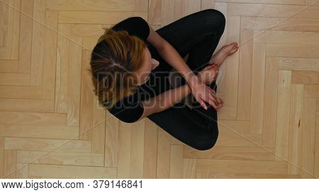 Top view of smiling woman sitting on floor and looking to camera.